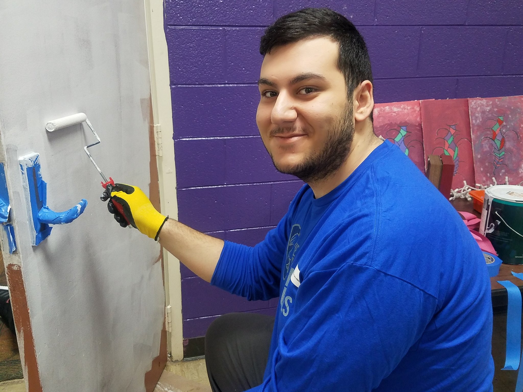 Faris Alkhouri smiling while painting a door white