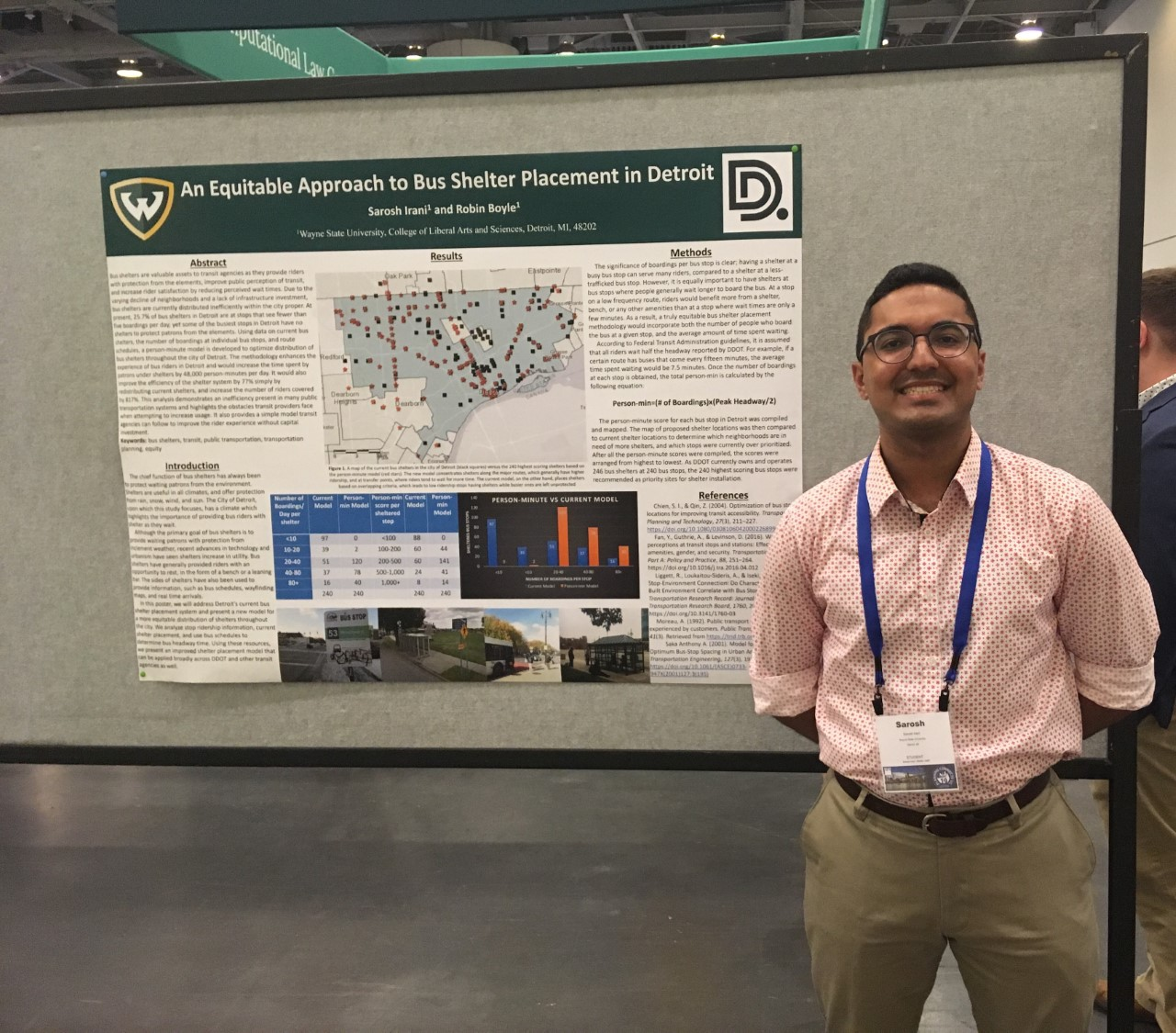 Sarosh Irani standing in front of gray display stand smiling with his research poster next to him